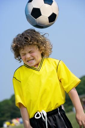 Boy heading soccer ball